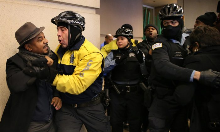 Willie Preston, left, scuffles with a police officer after he and other protesters tried to keep two women, partly seen at right, from attending the annual Interfaith Breakfast at the Hyatt Regency McCormick Place hotel in Chicago, Friday, Jan. 15, 2016. (Antonio Perez/Chicago Tribune via AP)