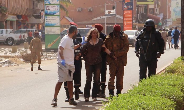 This image taken from AP television shows a woman being led to safety in Ouagadougou, Burkina Faso, on Jan. 16, 2016. (AP Photo)