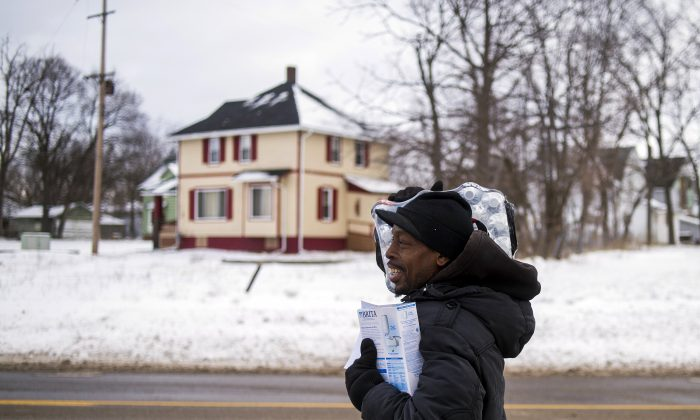 Flint resident Charles Chatmon carries a free water filter and case of water away from a fire station where members of the Michigan National Guard helped distribute supplies to aid in the city's water crisis, in Flint, Mich., on Jan. 13, 2016. Flint's tap water became contaminated with too much lead after the city switched its water supply in 2014 to save money while under state financial management. (Jake May/The Flint Journal-MLive.com via AP)