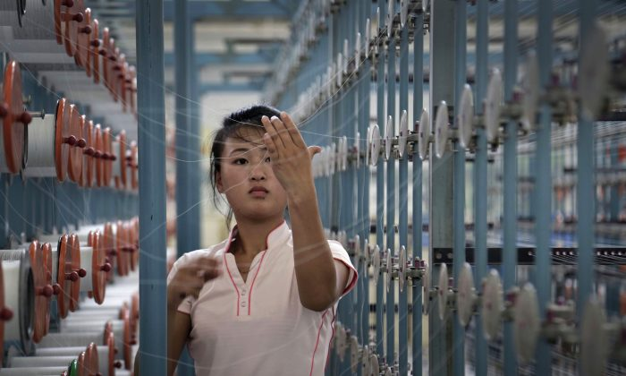 A North Korean woman works at the Kim Jong Suk Pyongyang textile factory, in Pyongyang, North Korea, on July 31, 2014. After ringing in the new year with claims of its first successful hydrogen bomb test, North Korea is now calling on the United States and the world community to accept it as a nuclear power, jettison the pursuit of punitive sanctions and allow it to focus on what it really wants: build up the nation's troubled economy. (AP Photo/Wong Maye-E)