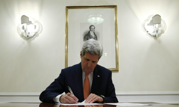Secretary of State John Kerry signs a series of documents in Vienna, Austria, on Jan. 16, 2016. Kerry confirms Iran in compliance with nuclear deal and lifts U.S. nuclear-related sanctions. (Kevin Lamarque/AP)