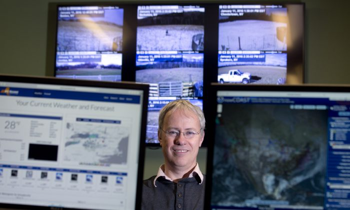 """In this Monday, Jan. 11, 2016 photo, Professor Chris Thorncroft, chairman of the Atmospheric and Environmental Sciences Department at the University at Albany and co- principal investigator for the New York State Mesonet, poses in the Mesonet operations center at the university in Albany, N.Y. Described as the new """"gold standard"""" of automated systems, the long-planned network of 125 weather stations stretching from the shores of Lake Erie to the tip of Long Island is expected to be completed by the end of the year. Thorncroft is helping lead the development of the New York State Mesonet, which is being funded with a $23.6 million grant from the Federal Emergency Management Agency. (AP Photo/Mike Groll)"""