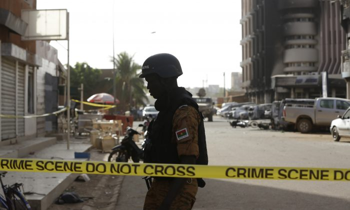 A soldier stand guards outside the Splendid Hotel in Ouagadougou, Burkina Faso, on Jan. 16, 2016. The overnight seizure of a luxury hotel in Burkina Faso's capital by al-Qaida-linked extremists ended Saturday when Burkina Faso and French security forces killed four jihadist attackers and freed more than 126 people, the West African nation's president said. (AP Photo/Sunday Alamba)