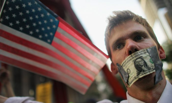 Americans aged 18 to 29 face an unemployment rate of 8 percent compared to 3.7 percent for those over 29, a study says. A protester wears a dollar bill over his mouth at the start of a march by demonstrators opposed to corporate profits on Wall Street in New York City on Sept. 30, 2011. (Mario Tama/Getty Images)