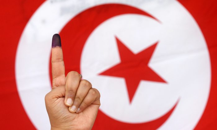 A Tunisian woman raises her ink-stained finger in front of a national flag after casting her vote in the country's first post-revolution presidential election on Nov. 23, 2014, at a polling station in the capital Tunis. (Fadel Senna/AFP/Getty Images)