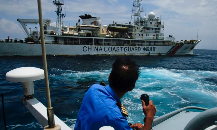 "Chinese ""little blue men"" maritime militia in the South China Sea. A member of the Malaysian Navy in a communication exchange with a Chinese Coast Guard ship in the South China Sea, near Kuantan, Malaysia, on March 15, 2014. (Rahman Roslan/Getty Images)"