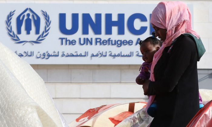 A Sudanese refugee from Darfur walks past tents during an open-ended sit-in outside the United Nations High Commissioner for Refugees (UNHCR) in the Jordanian capital Amman on Dec. 12, 2015, demanding better treatment and acceleration of their relocation. (Khalil Mazraawi/AFP/Getty Images)