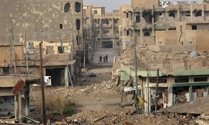 Civilians walk near rubble in the center of Ramadi in Iraq's Anbar Province on Jan. 30, 2007. (John Moore/Getty Images)