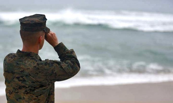 A Marine Officer attached to Marine Heavy Helicopter Squadron 463 uses binoculars to search for debris of a helicopter mishap in Haliewa Beach Park, Hawaii, on Jan. 15, 2016. Rescuers battled winds of up to 23 mph and waves up to 30 feet as they searched for 12 Marines who are missing after two helicopters they were in crashed off the Hawaiian island of Oahu. (Cpl. Ricky S. Gomez/U.S. Marine Corps via AP)