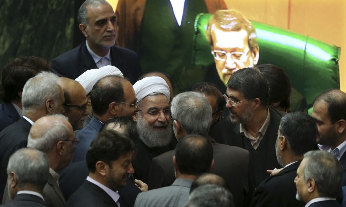"""Iranian President Hassan Rouhani (C) is surrounded by lawmakers as he leaves the parliament after presenting draft of the country's next year budget and sixth development plan in Tehran, Iran, on Jan. 17, 2016. Rouhani said Sunday that the official implementation of the landmark deal reached between Tehran and six world powers has satisfied all parties except radical extremists. Rouhani said the deal has """"opened new windows for engagement with the world."""" (AP Photo/Vahid Salemi)"""