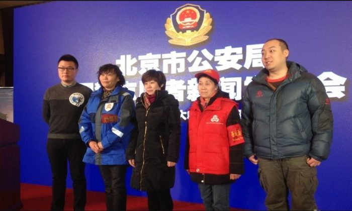 """From left to right, representatives from a variety of Party-affiliated voluntary groups: the """"Online Police Volunteers,"""" the """"Fengtai Persuasion Team,"""" """"Haidian Mobile Friends,"""" """"Xicheng Moms"""" and """"Chaoyang People"""" pose for a photo at a news conference at the Beijing Public Security Bureau on Jan. 13, 2016. (www.usachinapress.com)"""