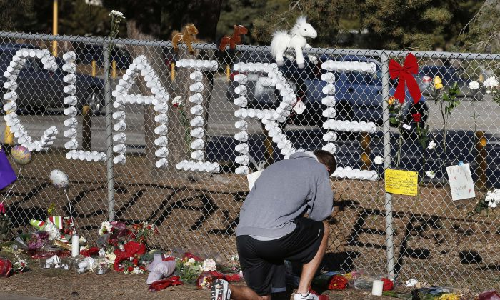 In this Dec. 16, 2013, file photo, Parker Semin, a 2011 Arapahoe High School graduate, prays at a makeshift memorial bearing the name of student Claire Davis, who was shot by Karl Pierson, a classmate during school three days earlier in an attack, in front of Arapahoe High School in Centennial, Colo. Legislation to allow lawsuits against Colorado schools for cases of violence  was signed into law Wednesday, June 3, 2015, by Gov. John Hickenlooper. (AP Photo/Brennan Linsley, File)