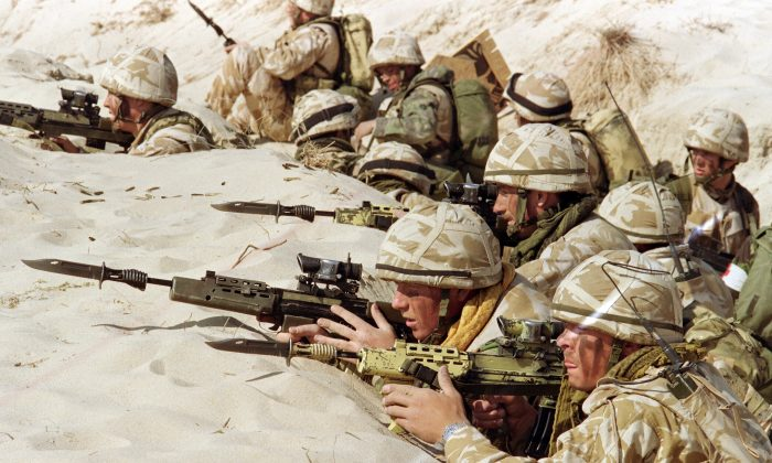 """British soldiers from the First Stafford, also known as the """"Desert Rats,"""" stand in a trench somewhere in Saudi desert, ready to attack during a live ammunition exercise, featuring the capture of an Iraqi positions, on Jan. 6, 1991. (Patrick Baz/AFP/Getty Images)"""
