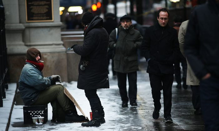 eople walk past a panhandler during a morning snow storm on December 17, 2013 in New York City. (Spencer Platt/Getty Images)