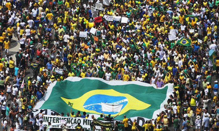 Anti-government protesters march carrying a Brazilian flag along Copacabana beach in Rio de Janeiro, Brazil, on March 15, 2015. Millions protested across the country against President Dilma Rousseff's government and the ruling Workers' Party, with many calling for Rousseff's impeachment. A massive corruption scandal at Brazil's state-owned oil company Petrobras has rocked the government and Dilma's approval ratings—now below 8 percent. Brazil's inflation rate has hovered around ten-year highs recently while the currency, the Brazilian real, has passed twelve-year lows when measured against the U.S. dollar. (Mario Tama/Getty Images)