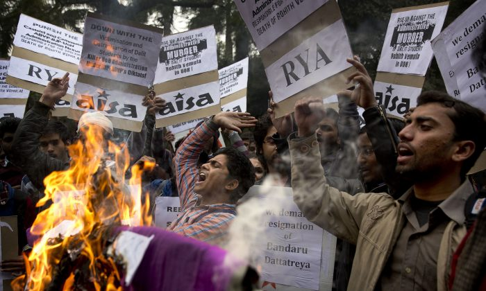 Indian students shout slogans and burn effigies of Hyderabad University's vice chancellor and a federal minister while protesting the death of an Indian student who, along with 4 others, was barred from using some facilities at his university in the southern tech-hub of Hyderabad, in New Delhi, India, (AP Photo/Manish Swarup)