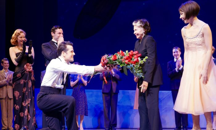 """In this Jan. 12, 2016, image released by Boneau/Bryan-Brown, actress Leslie Caron, who starred in the film, """"An American in Paris,"""" second right, is presented with flowers by Robert Fairchild as the rest of the cast, background from left, Jill Paice, Max von Essen and Leanne Cope (R) after a performance in New York. (Apples and Oranges Studios/Boneau/Bryan-Brown via AP)"""