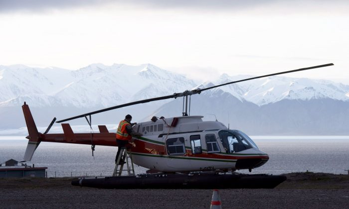 A worker checks on a helicopter at the airport in Pond Inlet, Nunavut, Aug. 23, 2014. A government advisory group is calling for significant investment in northern infrastructure. (THE CANADIAN PRESS/Adrian Wyld)