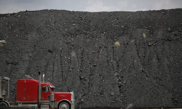 A tractor trailer drives by a mound of coal after delivering a truckload of coal to Arch Coal Terminals in Cattletsburg, Kentucky, on June 3, 2014. (Luke Sharrett/Getty Images)