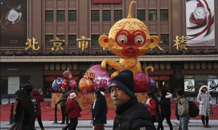Chinese pedestrians walk passed a display for the upcoming Year of the Monkey for the Chinese New Year at a market on Jan. 19, 2016 in Beijing. (Kevin Frayer/Getty Images)
