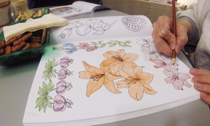 In this Dec. 14, 2015 photo, Carol Hensen colors at the DeForest Public Library in DeForest, Wis. Libraries and other groups nationwide are setting up get togethers for adults to color as the practice of coloring becomes more and more popular. (AP Photo/Carrie Antlfinger)