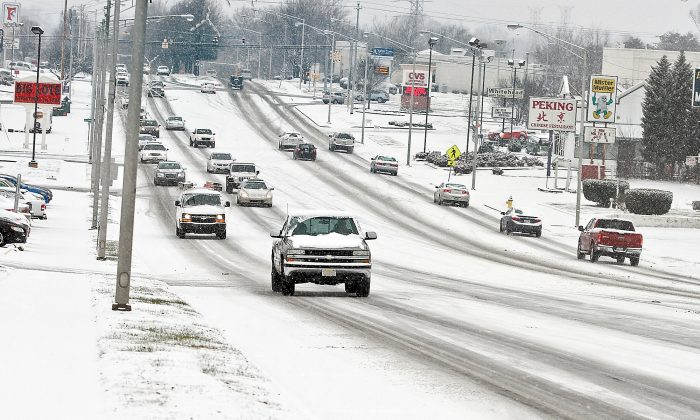 Traffic moves slowly along Hall Road Wednesday, Jan. 20, 2016, as snow falls making roads slippery, in Alcoa, Tenn. As the South and East braced for a nor'easter with the potential for significant snowfall by week's end, snow began to blanket much of Kentucky and Tennessee and contributed to at least one traffic-related death Wednesday. (Tom Sherlin /The Daily Times via AP)