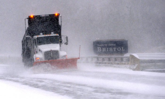 A snow plow works on clearing the Volunteer Parkway as snow falls, Wednesday, Jan. 20, 2016, in Bristol, Tenn. (Earl Neikirk/The Bristol Herald-Courier via AP)