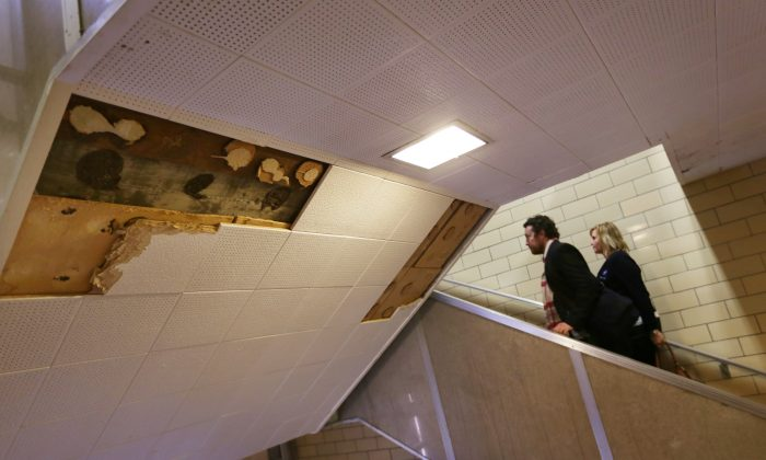 In this photo taken Thursday, Jan. 14, 2016, Pam Barnes, right and Asher Huey, of the American Federation of Teachers, walk by some missing ceiling tiles while touring Osborn Collegiate Academy of Mathematics Science and Technology in Detroit, to look at some of the poor conditions that have prompted sickouts by Detroit Public School teachers.(Romain Blanquart/Detroit Free Press via AP)