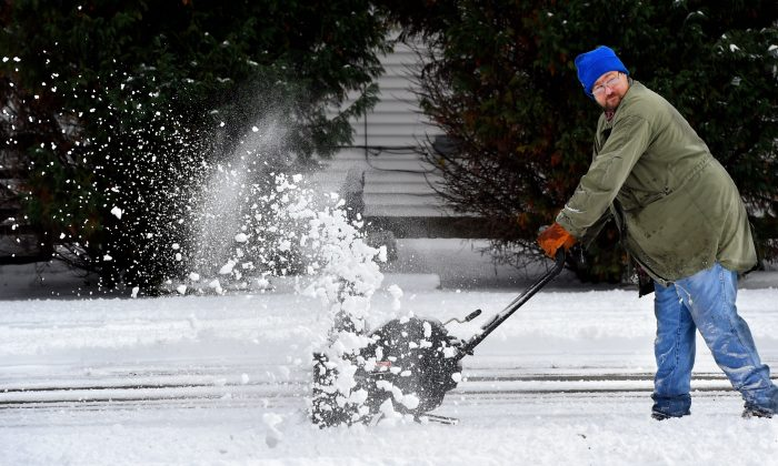 John Beach uses a snowblower to clear off a church parking lot on Letcher Street in Henderson, Ky.,following a three inch snow blanketing the area, Wednesday, Jan. 20, 2016. (Mike Lawrence/The Gleaner via AP)