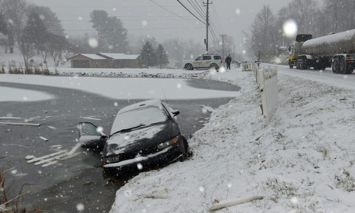 A driver lost control of her car and crashed through a fence and into a pond an Walnut Hill Road in Sullivan County near Bristol, Tenn., Wednesday, Jan. 20, 2016. during an afternoon snowfall. The driver was able to get out the passenger side and walk to a local business to call the Sheriff's Deptartment for help. (Earl Neikirk/The Bristol Herald-Courier via AP)