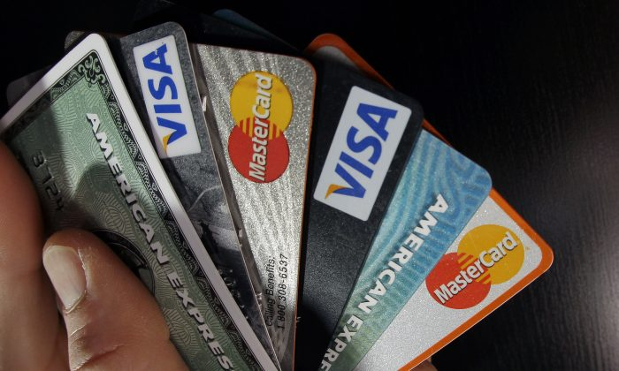 Consumer credit cards are posed in North Andover, Mass., on March 5, 2012. The biggest months for adding and dropping credit cards are November, December, and January, so now's the time to make sure the annual fee is really worth it. (AP Photo/Elise Amendola)