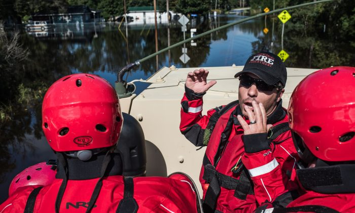 A rescue team takes a ride in an Army National Guard transport vehicle in the Brown's Ferry community October 11, 2015 near Georgetown, South Carolina. (Sean Rayford/Getty Images)