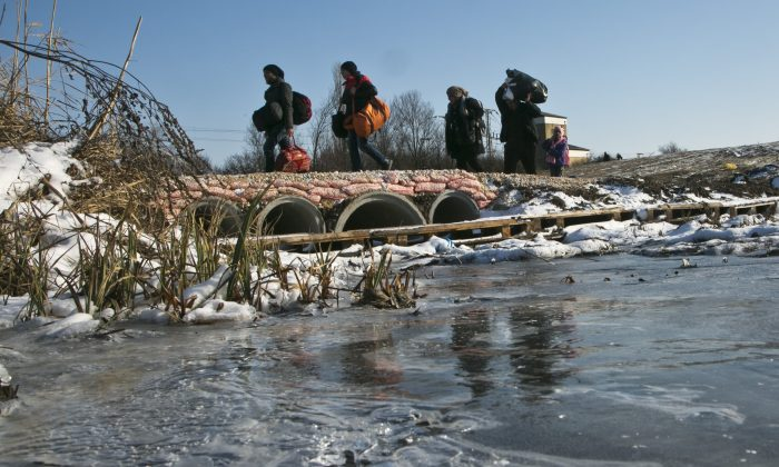 Migrants carrying their belongings across a partially frozen stream as they walk from the Macedonian border into Serbia, near the village of Miratovac, Serbia, on Tuesday, Jan. 19, 2016.  (AP Photo/Visar Kryeziu)