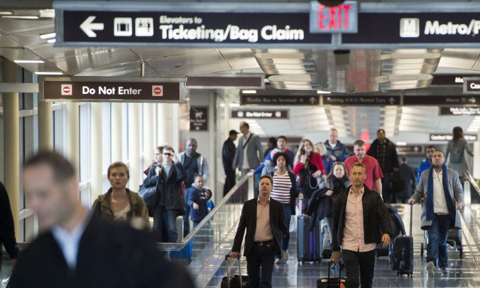 Passengers walk through a terminal after arriving at the Reagan National Airport in Arlington, Virginia, on Dec. 23, 2015. (Saul Loeb/AFP/Getty Images)