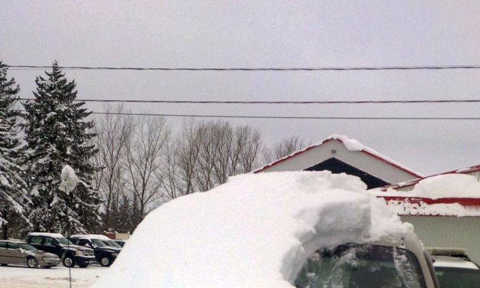 A snow covered vehicle in Brussels, Ontario, on Jan. 19, 2016. An 80-year-old man has been charged after driving the car that was almost completely covered in snow with only the driver's side windshield visible. (Sgt. Russell Nesbitt/Ontario Provincial Police via AP)