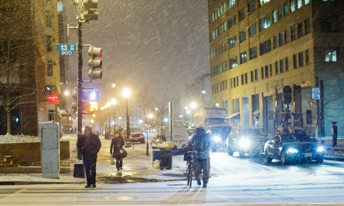 Pedestrian wait to cross 13th street in downtown Washington during an evening snowfall on Jan. 20. (AP Photo/Pablo Martinez Monsivais)