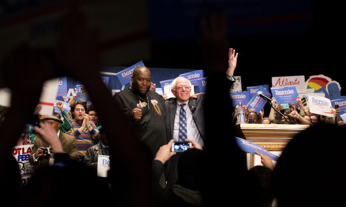 Democratic presidential candidate Sen. Bernie Sanders, I-Vt., right, waves to the crowd while standing with rapper Killer Mike after speaking onstage at a campaign event at the Fox Theatre Monday, Nov. 23, 2015, in Atlanta. (AP Photo/David Goldman)