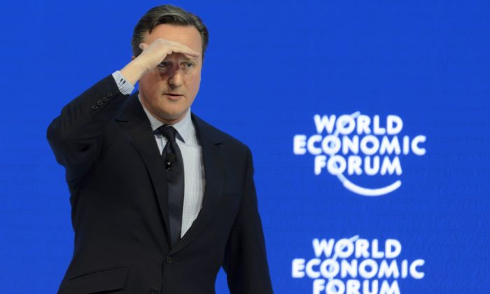 British Prime Minister David Cameron protects his eyes as he speaks during a panel session at the 46th Annual Meeting of the World Economic Forum, WEF, in Davos, Switzerland, Thursday, Jan. 21, 2016. (Laurent Gillieron/Keystone via AP)
