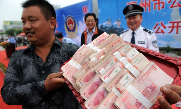 A businessman showing off his cash which was stolen and then returned to him by the police after a crackdown on a criminal gang in Bozhou, in eastern China's Anhui province. on September 14, 2011. (STR/AFP/Getty Images)