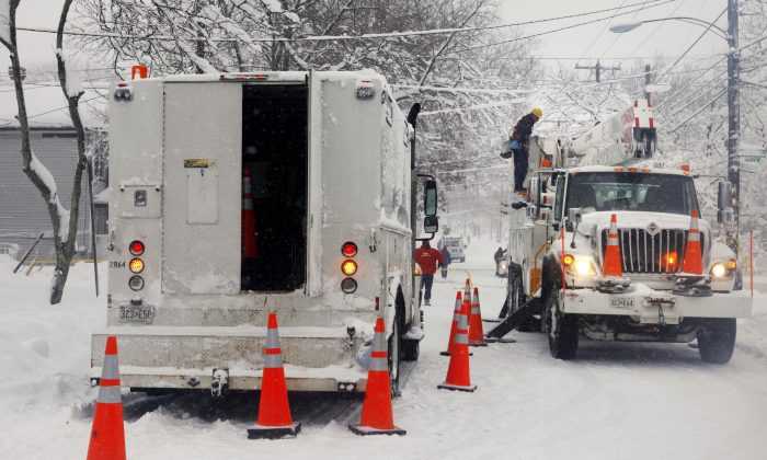 Pepco employees work aboard their service trucks to restore electric power to customers truck, right, works in Washington Saturday, Feb. 6, 2010, after a massive snow storm has hit the area causing power outages across the region. (AP Photo/Jacquelyn Martin)