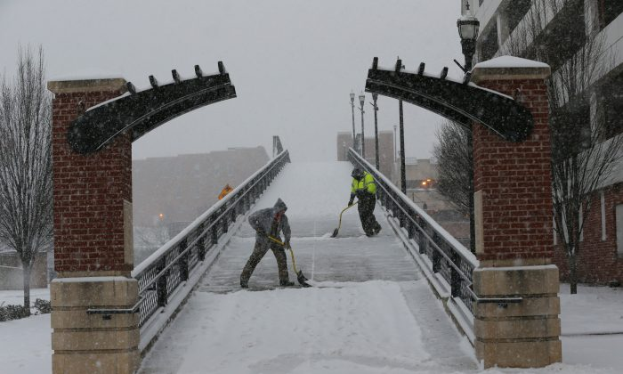 Kenny Hamblin (L) and Andrew Watts with the Roanoke Parks and Recreation Department shovel snow on the Martin Luther King bridge on First Street and Salem Avenue as snow falls Friday morning in Roanoke, Va., on Jan. 22, 2016. A blizzard menacing the Eastern United States started dumping snow in Virginia, Tennessee and other parts of the South on Friday as millions of people in the storm's path prepared for icy roads, possible power outages and other treacherous conditions. (Stephanie Klein-Davis/The Roanoke Times via AP)