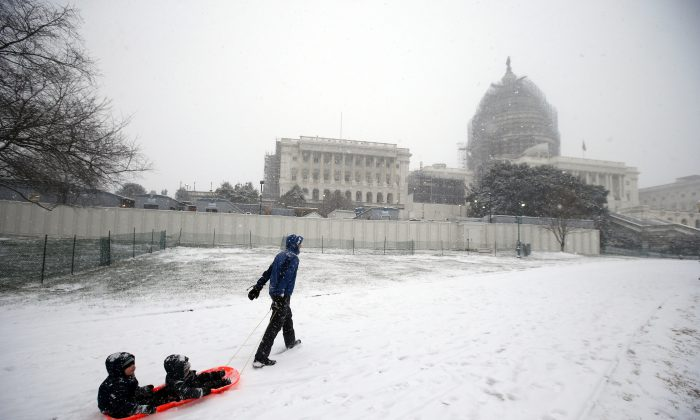 Ben Cichy pulls a sled with his sons Adrian, 18-months-old, and Logan 3, inside as they head for sledding in the snow on Capitol Hill, on Jan. 22, 2016. (AP Photo/Alex Brandon)