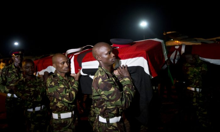 Military pallbearers carry the coffins of four Kenyan soldiers who were killed in Somalia, at a ceremony to receive their bodies which were airlifted to Wilson Airport in Nairobi, Kenya Monday, Jan. 18, 2016. Kenyan officials have not said how many soldiers were killed when Islamic extremist fighters attacked a base for African Union peacekeepers in southwestern Somalia on Friday. (AP Photo/Ben Curtis)