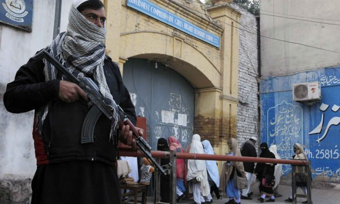 Security guards stand alert around schools and colleges following an attack on Bacha Khan University, in Peshawar, Pakistan, Thursday, Jan. 21, 2016. (AP Photo/Mohammad Sajjad)