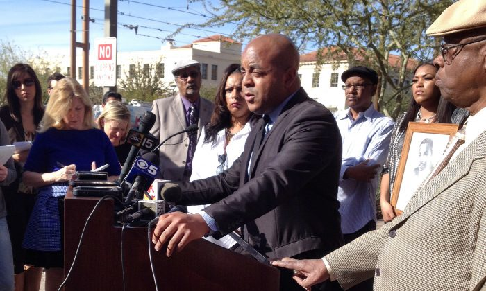 Rev. Jarrett Maupin (C), an Arizona civil rights activist, speaks during a news conference in Phoenix on Jan. 21, 2014, after an Arizona State University fraternity hosted a distasteful party in commemoration of Martin Luther King Jr. Day, replete with racist stereotypes and offensive costumes. Maupin is calling on the school to expel all students involved and permanently ban the Tau Kappa Epsilon fraternity from campus. (AP Photo/Brian Skoloff)