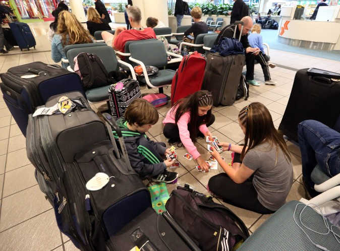 Liam Everett (L), 8, Chloe Betts (C), 10, and Isabella Everett, 10, of North Carolina, play a card game, at Orlando International Airport in Orlanda, Fla., on Jan. 22, 2016. (Red Huber/Orlando Sentinel via AP)