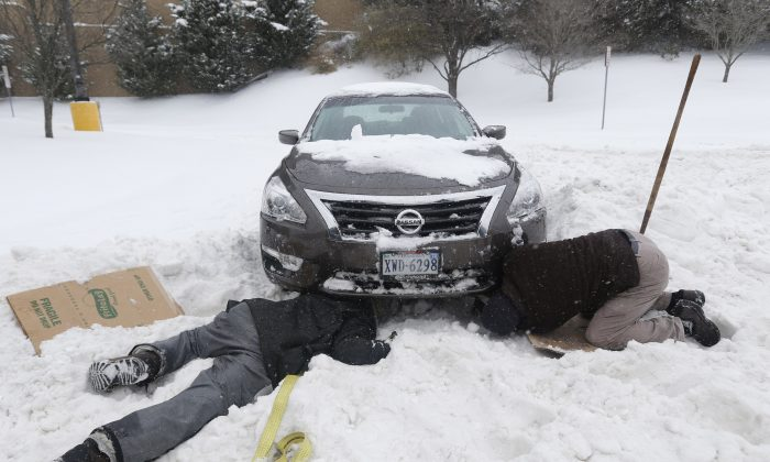 Mike Aliff, left,of Richmond, hooks up a tow strap to Paul Kay's, right, car that is stuck in the snow in Richmond, Va., Saturday, Jan. 23, 2016. Good Samaritan Aliff had helped six other motorists. Portions of Virginia are under a blizzard warning. (AP Photo/Steve Helber)