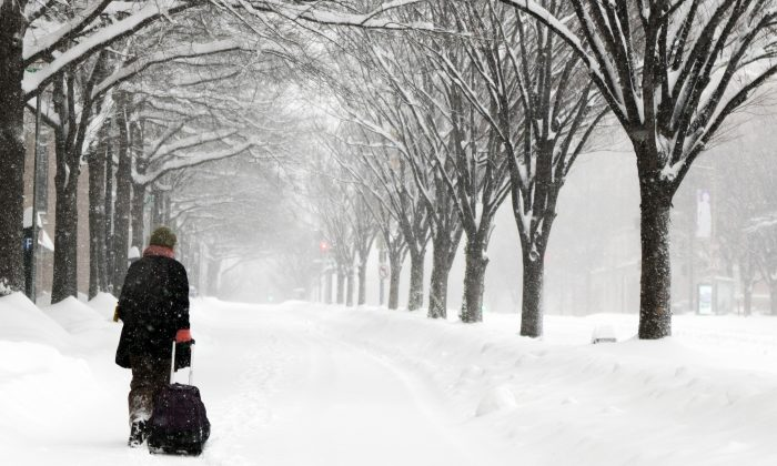Michelle Navarre Cleary pulls a bag as she walks on K Street in Washington, D.C., on Jan. 23, 2016, as snow continues to fall. With long lead time from forecasters and stern warnings from authorities, tens of millions of residents from northern Georgia to New Jersey shuttered themselves inside to wait out a mammoth storm that made travel treacherous and could dump 2 feet or more of snow in some areas. (AP Photo/Jon Elswick)