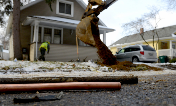 As the hole is filled in in the background, a piece of an old lead water pipe sits next to a new copper pipe at a home on Greencroft in Lansing, Mich., on Jan. 22, 2016. (Dave Wasinger/Lansing State Journal via AP)