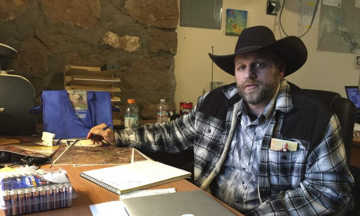 Ammon Bundy sits at a desk he's using at the Malheur National Wildlife Refuge in Oregon on Jan. 22, 2016. Bundy is the leader of an armed group occupying a national wildlife refuge to protest federal land policies. The leader of an armed group occupying the refuge met briefly with a federal agent Friday, but left because the agent wouldn't talk with him in front of the media. (AP Photo/Keith Ridler)